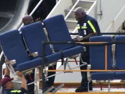 workmen carrying airplane seats