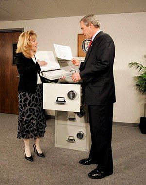 George Bush looks at binders of Social Security IOUs
