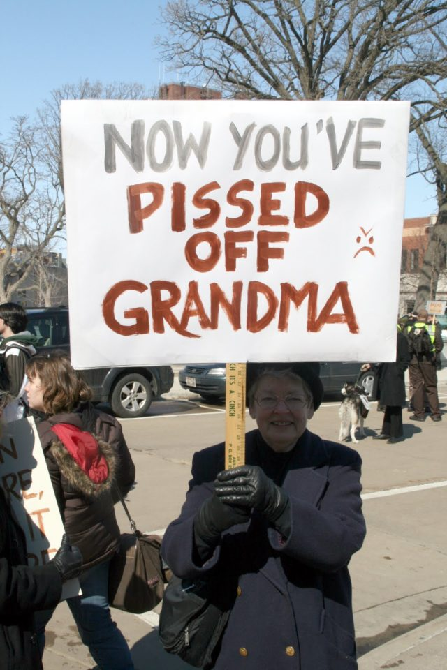 "Protestor with sign ""Now you've pissed off Grandma"""